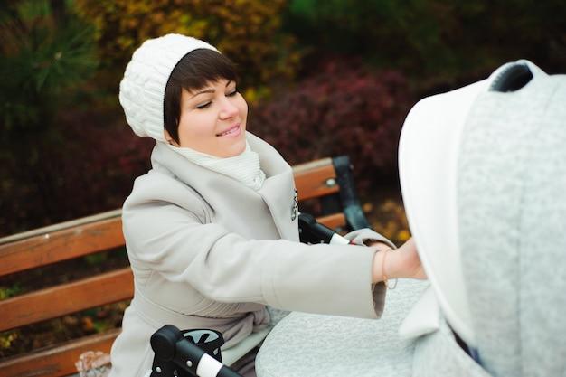 Paseo familiar en el parque de otoño con un cochecito. mamá y bebé al aire libre Foto Premium