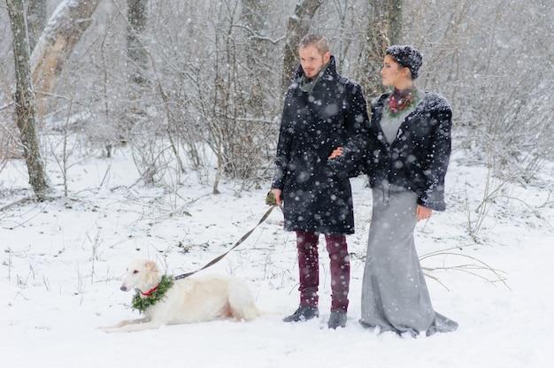 Paseo de invierno en una tormenta de nieve con un perro Foto Premium