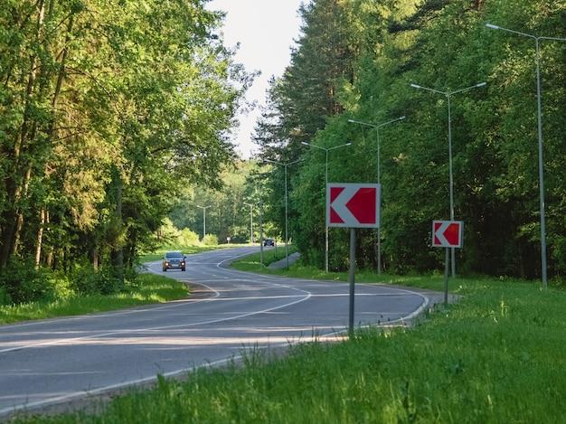 Paseos en auto en la sinuosa carretera en un bosque de verano Foto Premium