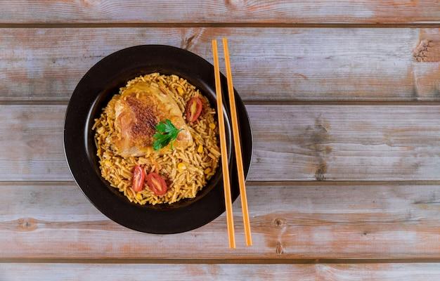 Pasta y arroz con pollo y verduras en un tazón negro. Foto Premium