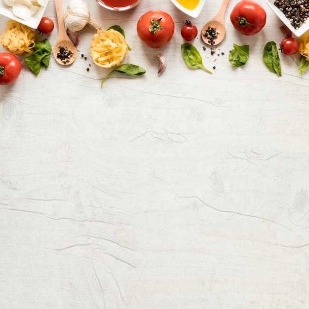 Pasta cruda y sus ingredientes dispuestos en fila sobre mesa de madera blanca Foto gratis