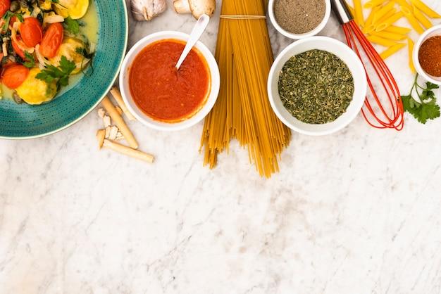 Pasta e ingredientes de pasta sobre fondo de mármol con textura Foto gratis