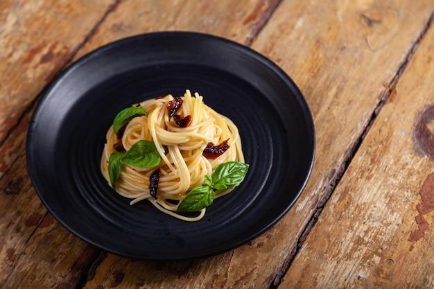 Pasta de espagueti con verduras, pimienta, hojas de albahaca en un plato redondo negro sobre fondo de madera vintage rústico marrón Foto Premium