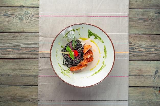 Pasta fresca de tagliolini negro con pollo en hierbas sobre rúcula y tomate Foto Premium