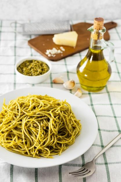 Pasta italiana con botella de aceite de oliva y queso Foto gratis