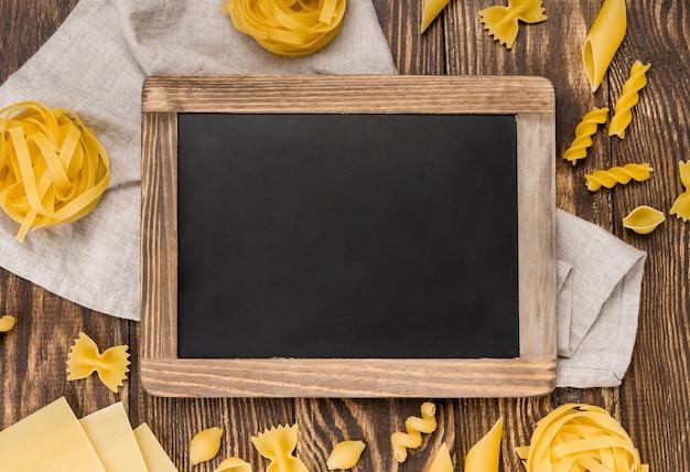 Pasta italiana en cucharas al lado de pizarra Foto gratis