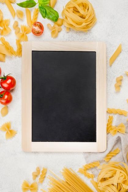 Pasta italiana y tomates al lado de pizarra Foto gratis