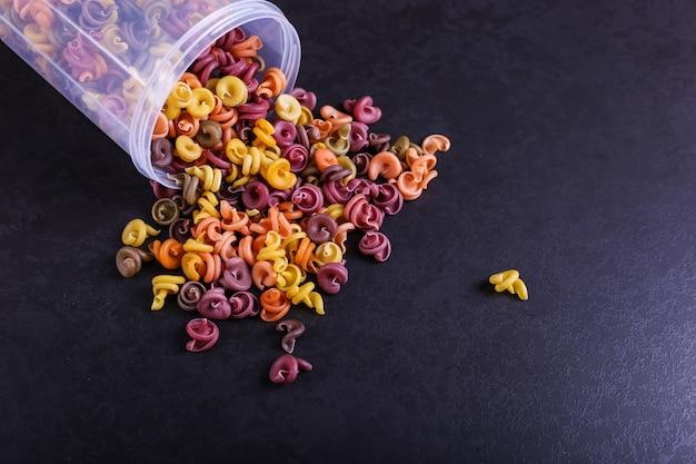 Pasta multicolor con la adición de colorante vegetal natural. dispersos de una lata sobre una mesa de hormigón negro Foto Premium