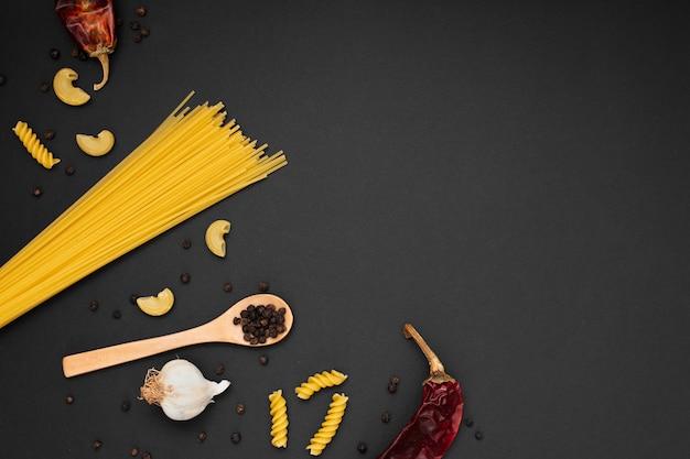 Pasta plana sin cocer con ingredientes de cuchara de madera y espacio de copia Foto gratis