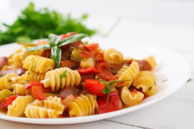 Pasta con salsa de tomate con salchicha, tomate, albahaca verde decorada en plato blanco sobre una mesa de madera. Foto gratis