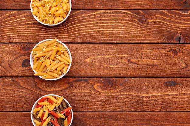 Pasta seca en el fondo de la mesa de madera Foto Premium