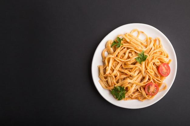 Pasta de sémola con salsa de tomate al pesto, naranja y hierbas. vista superior, copyspace Foto Premium