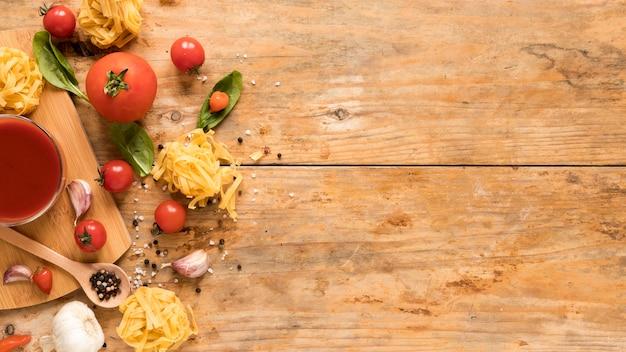 Pastas crudas de los tallarines cerca de sus ingredientes y salsa de tomate sobre fondo de madera texturizado Foto gratis