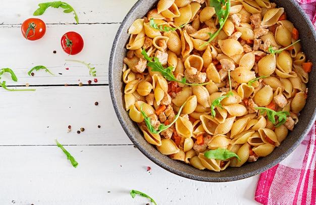 Pastas italianas de pasta con carne y salsa de tomate. pasta conchiglie. vista superior Foto Premium