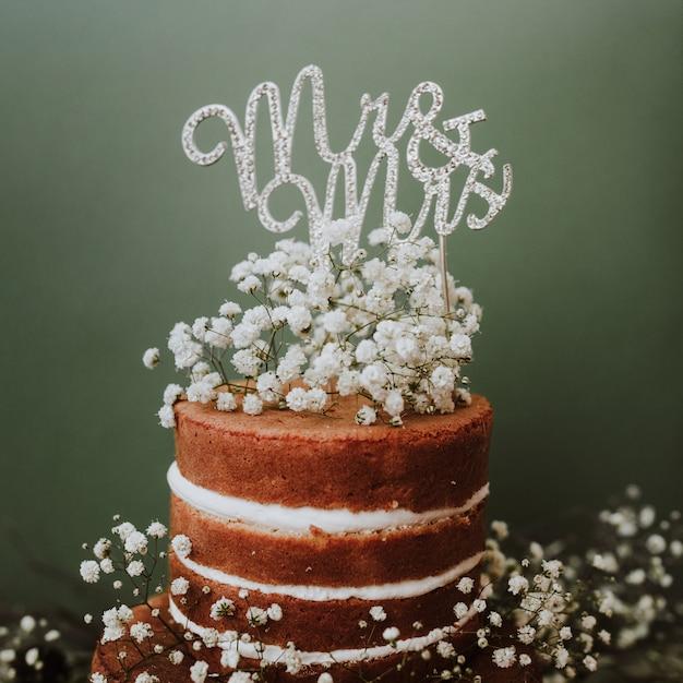 Pastel de bodas con decoración de paniculata y sr. y sra. topper sobre fondo verde Foto gratis