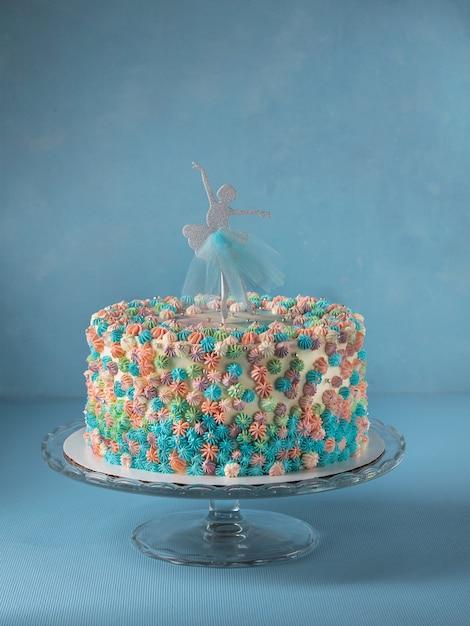Pastel de capas de cumpleaños decorado con adorno de pastel de bailarina sobre fondo azul cielo Foto Premium
