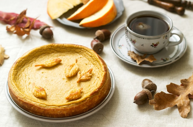 Pastel casero tradicional de calabaza estadounidense, decorado con galletas sobre un fondo de calabazas y hojas de otoño. Foto Premium