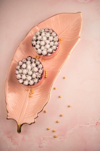 Pastel de chocolate cremoso con bayas en hojas de cerámica rosa sobre fondo texturizado Foto gratis