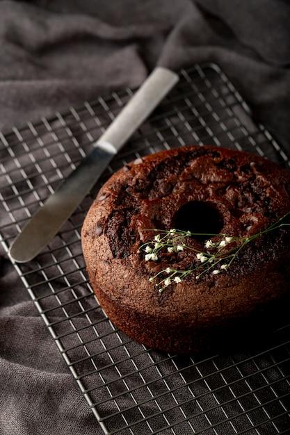Pastel de chocolate sobre un fondo gris con un cuchillo Foto gratis