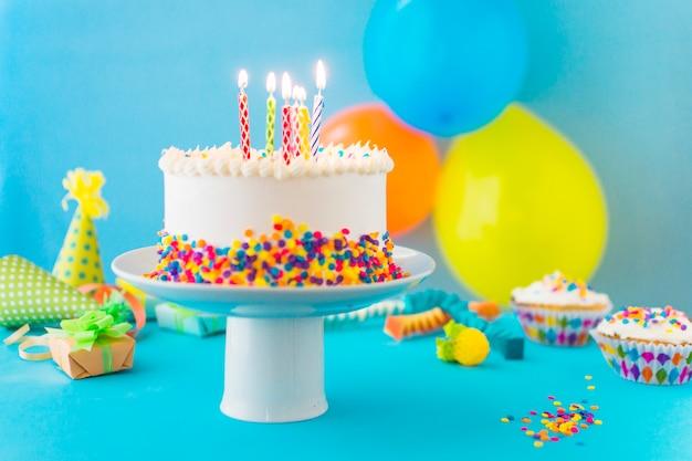 Pastel decorativo con vela iluminada en cakestand. Foto gratis