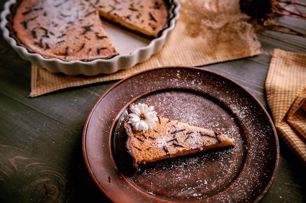 Pastel horneado en forma de cerámica espolvoreado con rodajas de chocolate sobre una mesa de madera. rebanada de pastel colocada en plato de arcilla y decorada con flores Foto Premium