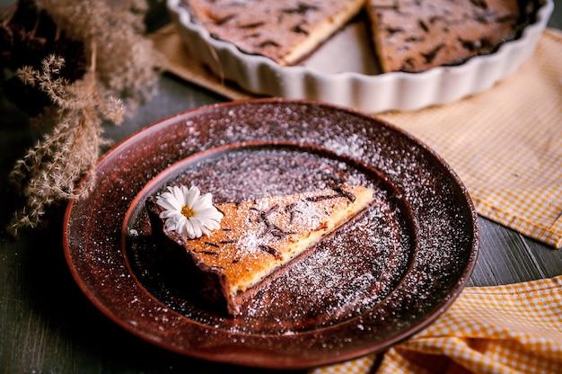 Pastel horneado en forma de cerámica espolvoreado con rodajas de chocolate sobre una mesa de madera. Foto Premium