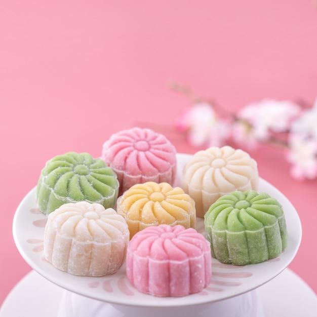 Pastel de luna colorido para el festival del medio otoño sobre fondo rosa Foto Premium