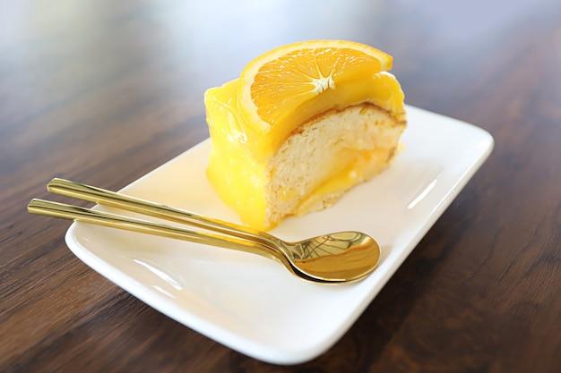 Pastel de naranja con cobertura de naranja en un plato blanco sobre la mesa de madera. Foto Premium