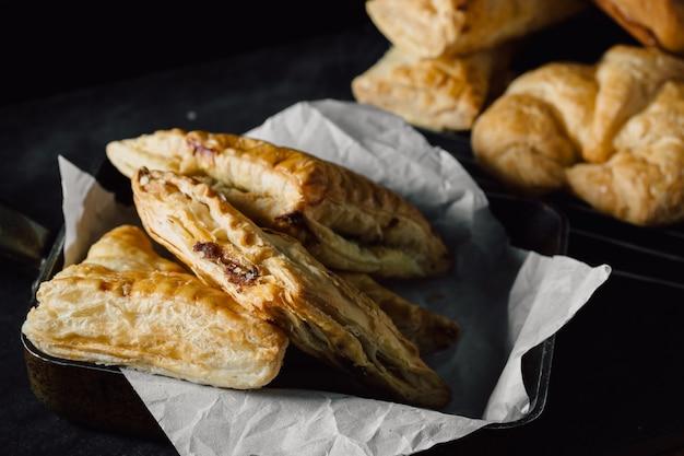 Pastel de pollo en la mesa negra en el cuarto oscuro Foto Premium
