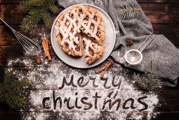 Pastel rebanado con mensaje de feliz navidad Foto gratis