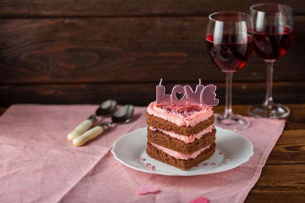 Pastel con velas y copas de vino. Foto gratis