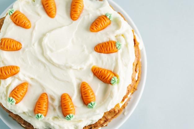 Pastel de zanahoria de pascua con glaseado en mesa azul Foto gratis
