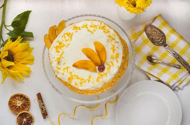 Pastel de zanahoria. pastel de zanahoria en un plato blanco decorado con ralladura de naranja y duraznos con flores amarillas. vista desde arriba. pasteles caseros Foto Premium