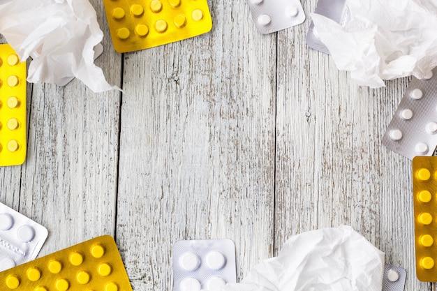 Pastillas de borde. vitaminas, tabletas, píldoras en blister y pañuelos arrugados sobre fondo blanco de madera. Foto Premium