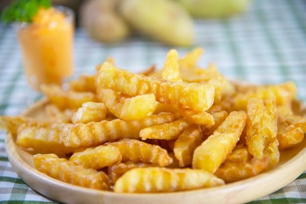 Patata frita deliciosa en un plato de madera con salsa bañada - concepto tradicional de comida rápida Foto gratis