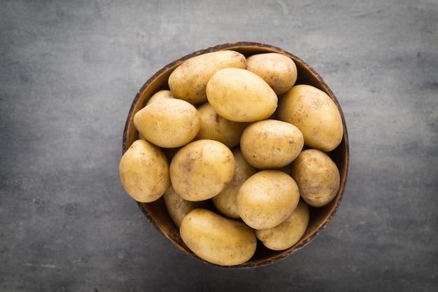 Patata nueva en el cuenco en gris Foto Premium