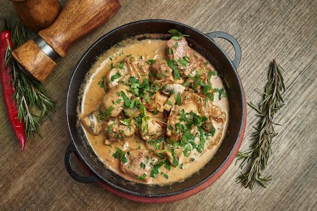 Patatas al horno con pollo en salsa cremosa en una sartén sobre una superficie de madera. vista superior de comida sabrosa Foto Premium
