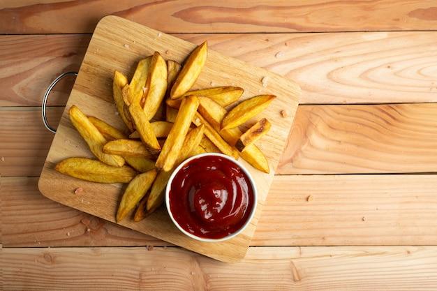 Patatas fritas caseras en mesa de madera Foto gratis
