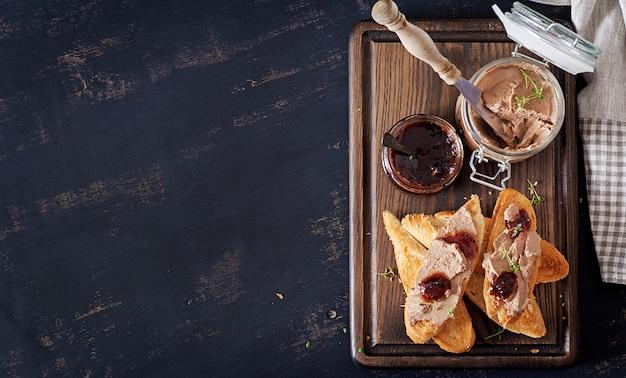 Paté de hígado casero de pollo en frasco de vidrio con tostadas y mermelada de arándano rojo con chile. Foto Premium