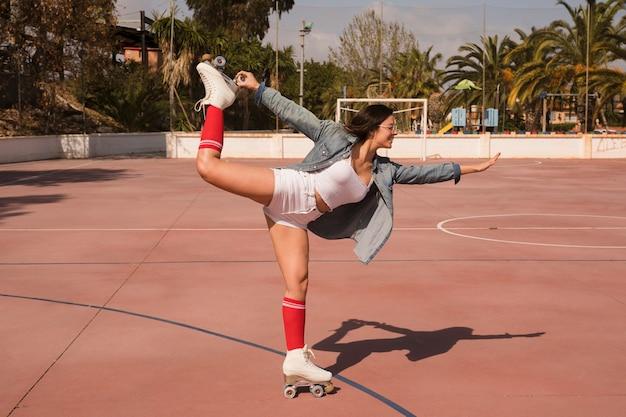 Patín de ruedas que lleva de moda de la mujer joven que se coloca en una pierna sobre la cancha de fútbol Foto gratis
