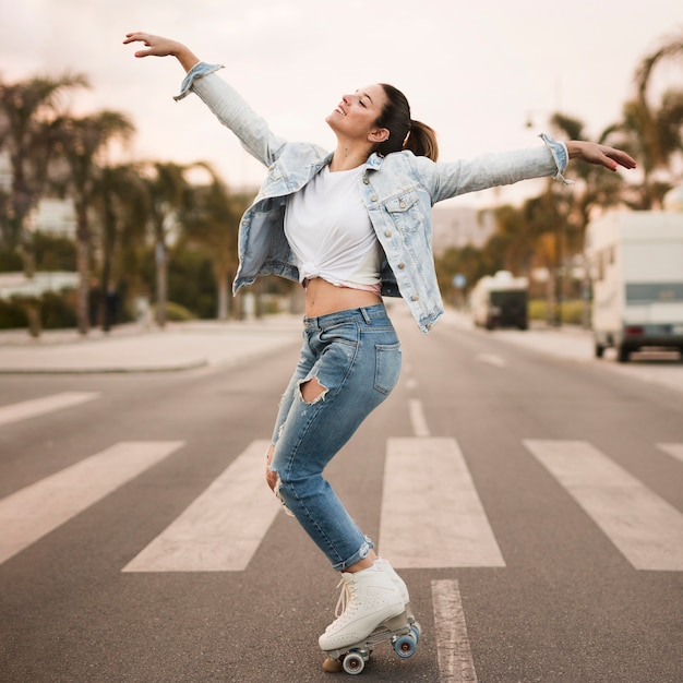 Patinador femenino joven sonriente que balancea en el paso de peatones Foto gratis