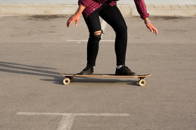 Patinador montando longboard sobre asfalto Foto gratis
