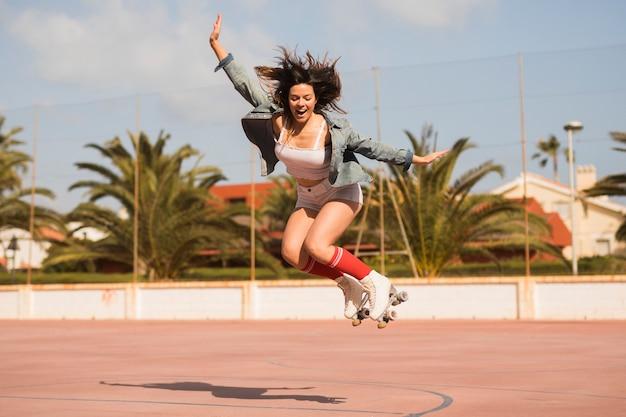 Una patinadora excitada saltando por encima de la pista al aire libre. Foto gratis