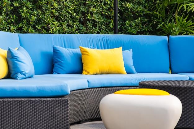 Patio al aire libre en el jardín con sillón y decoración de almohadas. Foto gratis