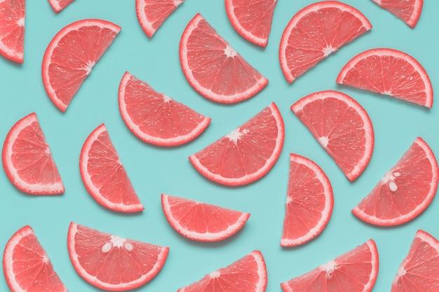 Patrón creativo de verano con rodajas de pomelo sobre fondo azul pastel Foto Premium