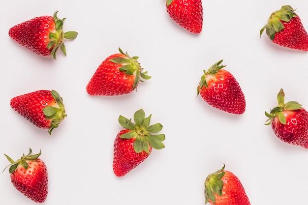 Patrón con fresas maduras sobre fondo blanco Foto gratis