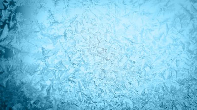 Patrón de navidad escarchado en un cristal de ventana de invierno Foto Premium