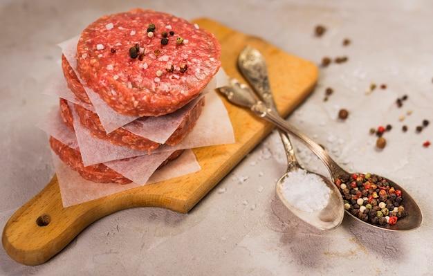 Patty hamburguesas en una tabla de madera con cucharas Foto Premium