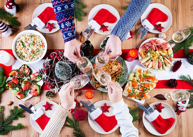 Pavo al horno. cena de navidad. la mesa navideña se sirve con un pavo, decorado con oropeles brillantes y velas. pollo frito, mesa. cena familiar. vista superior, manos en el marco Foto gratis