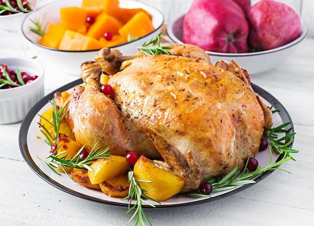 Pavo asado adornado con arándanos en una mesa de estilo rústico decorado hoja de otoño. día de gracias. pollo al horno. Foto Premium